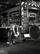 Les anges gardiens 2008. Un pompier manœuvrant une manivelle sur son camion.<br /> Photographie en noir et blanc.