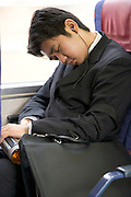 young businessman taking a nap on his way to work