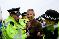 © Licensed to London News Pictures. 18/04/2019. London, UK. An environmental activist from Extinction Rebellion movement is detained by the police on Waterloo Bridge on the fourth day of their climate change protest. Photo credit: Dinendra Haria/LNP