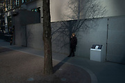 Woman on her cell phone beside a wall with a tree shadow within street scene of light and shadow in the City of London, England, United Kingdom.