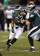 Philadelphia Eagles running back Chris Polk (32) appears to take a fake handoff from Philadelphia Eagles quarterback Nick Foles (9) during the NFL NFC Wild Card football game against the New Orleans Saints on Saturday, Jan. 4, 2014 in Philadelphia. The Saints won the game 26-24. ©Paul Anthony Spinelli