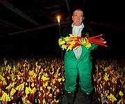 Portrait of Graham Oldroyd whilst pulling rhubarb in the forcing shed by candlelight, E. Oldroyd and sons Ltd, Carlton, Wakefield, West Yorkshire, UK. February is high season for the forced rhubarb of the so-called 'Rhubarb Triangle' formed by Wakefield, Rothwell and Morley. These intensely flavoured plants with pink stems and yellow leaves - grown by candlelight and tended by hand in huge, heated forcing sheds - are one of the first culinary delights of the British winter.