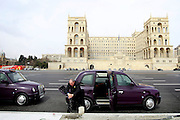 A taxi driver takes advantage of the fact of not having customers to clean his London alike cab, in front of the House of Government building. Azeri GDP grew 41.7% in the first quarter of 2007, possibly the highest of any nation worldwide, as the country economy completed its post-Soviet transition into a major oil based economy.<br /> Baku was awarded the right to host of the first European Games, a multi-sport event.