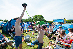 © Licensed to London News Pictures. 11/06/2015. Newport, UK.Festival goers play 'yard of ale' drinking games as they sit amongst their tents at Isle of Wight Festival 2015. Today has been hot and sunny.  This years festival include headline artists the Prodigy, Blur and Fleetwood Mac.  Photo credit : Richard Isaac/LNP