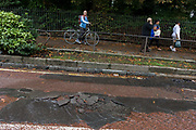 Londoners pass-by and look at the cracked road surface of tarmac, weeks after disastrous flooding in nearby Herne Hill, south London. Denmark Hill has been closed in both directions due to another burst water main in multiple locations across the road (A215) between the junctions of Champion Hill and Champion Park in south London. Water is seen running towards Kings College Hospital, 200m downhill and Denmark Hill is a major thoroughfare for the hospital's Accident & Amergency (A&E) department and used by ambulances and emergency traffic throughout the day and night.