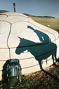 The shadow of a Mongolian horseman and a backpack belonging to a tourist in front of a guest yurt.