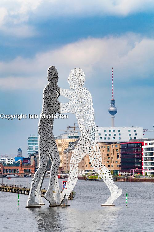 Skyline of Berlin across River Spree with large sculpture Molecule Man in Berlin Germany
