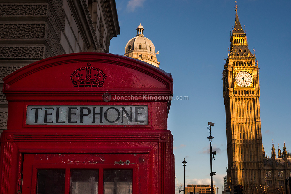 Low angle view of a red telephone booth and Big Ben, officially known as the Elizabeth Tower, against a blue sky in London, England.