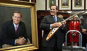 """TALLAHASSEE, FL. 4/29/04-House Speaker Johnnie Byrd, R-Plant City, picks up the Gibson Flying V guitar given to him by the House as he admires his portrait that will hang on the chamber wall during a ceremony honoring his term as speaker, Thursday at the Capitol in Tallahassee. Byrd, a classic rock aficionado, also received a rare Chuck Berry record with the song """"Johnny B. Goode"""" on it. House members traditionally honor their presiding officer with gifts at the close of their term. COLIN HACKLEY PHOTO"""