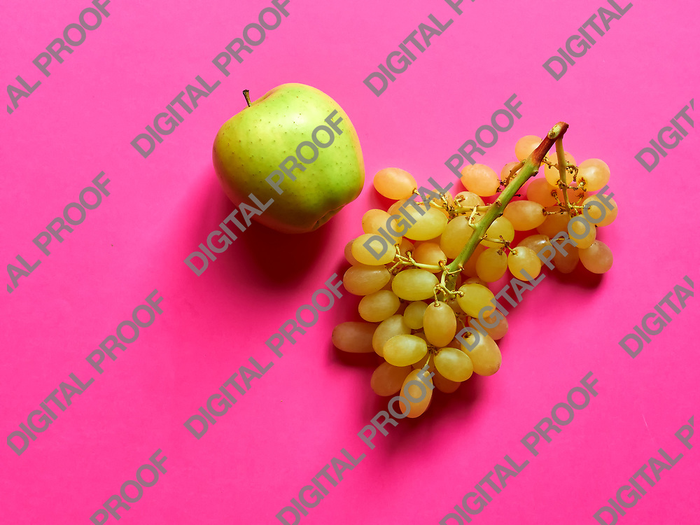 Green apple and bunch of green grapes isolated in studio against a fuschia background viewed from above