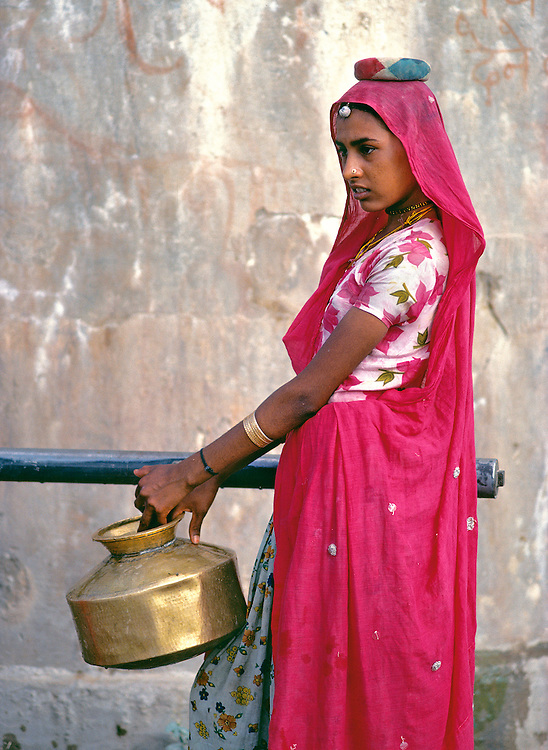 A sari-clad woman fills a brass pot at a country well in Rajasthan, India.
