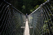 Zach Podell-Eberhardt crosses the suspension footbridge across Logan Creek, West Coast Trail, British Columbia, Canada.