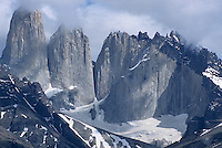Clouds lift to reveal the sheer cliffs of Torres del Paine National Park, (Patagonia region) Chile.
