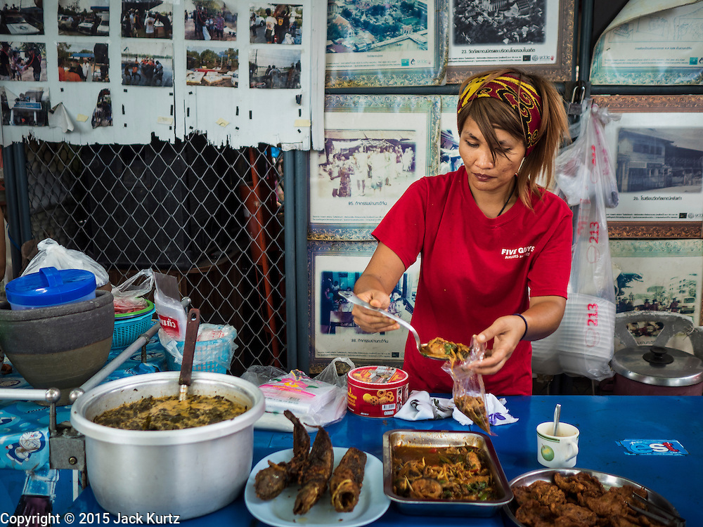 18 SEPTEMBER 2015 - BANGKOK, THAILAND: A woman sells homemade curries in front of a display of historic photos in the neighborhood at Wat Kalayanamit. She is being evicted and doesn't have a new location for her curry stand or a new home yet. Fiftyfour homes around Wat Kalayanamit, a historic Buddhist temple on the Chao Phraya River in the Thonburi section of Bangkok are being razed and the residents evicted to make way for new development at the temple. The abbot of the temple said he was evicting the residents, who have lived on the temple grounds for generations, because their homes are unsafe and because he wants to improve the temple grounds. The evictions are a part of a Bangkok trend, especially along the Chao Phraya River and BTS light rail lines. Low income people are being evicted from their long time homes to make way for urban renewal.             PHOTO BY JACK KURTZ