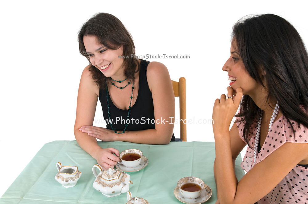 two multiracial female friends drinking tea