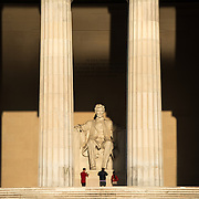 The early morning sun shines on the statue of Abraham Lincoln in the Lincoln Memorial in Washington DC.