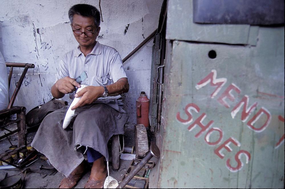 SHANGHAI, CHINA :  Shoe mender in a hutang area in Shanghai, China. Photograph by David Paul Morris