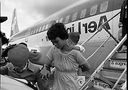 Vietnamese Refugees Arrive In Ireland.   (M85)..1979..09.08.1979..08.09.1979..9th August 1979..As part of an UNHCR initiative, Ireland agreed to take some of the Vietnamese (boat people) refugees into the country. A temporary refugee centre has been set up in the grounds of Blanchardstown Hospital to accomodate the families, from where they will be assimilated into the community..Image shows a young Vietnamese woman and her child being assisted down the aircraft stairs by an Aer Lingus air hostess after the plane had landed at Dublin Airport.