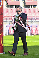 A league official take the SPFL Championship trophy to the podium after the final whistle of the SPFL Championship match between Heart of Midlothian and Inverness CT at Tynecastle Park, Edinburgh Scotland on 24 April 2021.