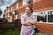 A young pregnant mother outside her house on a council estate in Leyland, Lancashire.