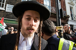 London, UK. 10th June, 2018. One of a group of Orthodox Haredi Jews from Neturei Karta is abused by pro-Israel activists (out of picture) as he arrives to take part in the pro-Palestinian Al Quds Day march through central London organised by the Islamic Human Rights Commission. An international event, it began in Iran in 1979. Quds is the Arabic name for Jerusalem.