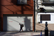 An elementary school boy, wearing school uniform and a surgical  face-mask against COVID-19, walks home past a shuttered building in Ueno, Tokyo, Japan. Friday March 19th 2021