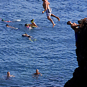 Cliff diving from Black Rock, an outcropping of lava rocks on Ka'anapali Beach in Maui, Hawaii. Swimmers jump from rocks that are about 80 feet into the ocean.