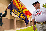 25 APRIL 2012 - PHOENIX, AZ:  BARRY SPINKA, a member of the Tea Party and a supporter of SB1070, waits for a Tea Party rally in support of SB1070 to start at the Arizona Capitol Wednesday. Immigrants' rights groups opposed to SB1070 and Tea Party affiliated groups that support SB1070 gathered at the state capitol in Phoenix Wednesday to express their opposition and support of the bill. SB1070 was signed by Arizona Governor Jan Brewer in April 2010. At the time it was the toughest anti-illegal immigration bill in the country. Immigrants' rights groups sued Arizona and the federal courts stopped enforcement of the bill. The bill ended up in the US Supreme Court which heard arguments Wednesday. A ruling on the bill is expected in June.    PHOTO BY JACK KURTZ