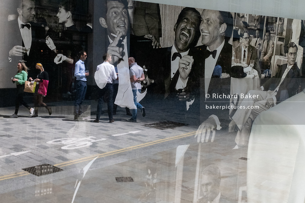 Merging with party images of the Rat Pack in the window of a menswear outfitters, are the reflections of City workers drinking outside on the pavement outside a pub on Lime Street in the City of London, the capital's financial district, on 29th July 2020, in London, England.