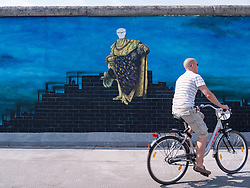 Man cycles past painting of Erich Honecker on wall at East Side Gallery part of former Berlin Wall in Berlin Germany