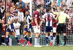 West Bromwich Albion's Dwight Gayle (left) is shown a second yellow card and sent off by referee Graham Scott (centre) during the game