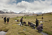 Kyrgyz men wash their hands after attending the funeral of Haji Osman Boi (one of the Rais-e Shura of the Pamir, a chief Council) in Andemin camp...Trekking through the high altitude plateau of the Little Pamir mountains (average 4200 meters) , where the Afghan Kyrgyz community live all year, on the borders of China, Tajikistan and Pakistan.