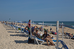 © Licensed to London News Pictures.  15/10/2021. Santa Luiza, Portugal. Holidaymakers enjoy a warm and sunny weather along Barril Beach in Santa Luza, Portugal. As double-jabbed travellers from the UK will no longer have to take a £75 PCR test on day two from October 24; instead they will be able to take a literal swab which costs £30. Photo credit: Marcin Nowak/LNP