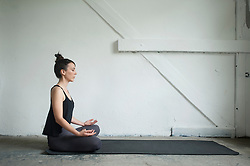 Side profile of a mid adult woman practicing lotus pose in yoga studio, Munich, Bavaria, Germany