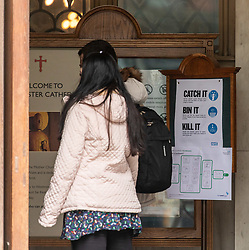 © Licensed to London News Pictures. 18/03/2020. London, UK. A couple walk past a Coronavirus Government safety sign at Westminster Cathedral as the majority of workers keep away from the centre of London as Coronavirus pandemic crisis continues. Photo credit: Alex Lentati/LNP