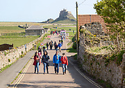 Line of people walking to and from Lindisfarne castle, Holy Island, Northumberland, England, UK