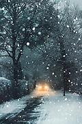 Headlights of a car driving through the snow