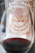 A glass of wine with the label of a bottle seen through the glass - label with vintage 2001 - Chateau Baron Pichon Longueville, Pauillac, Medoc, Bordeaux, Grand Cru