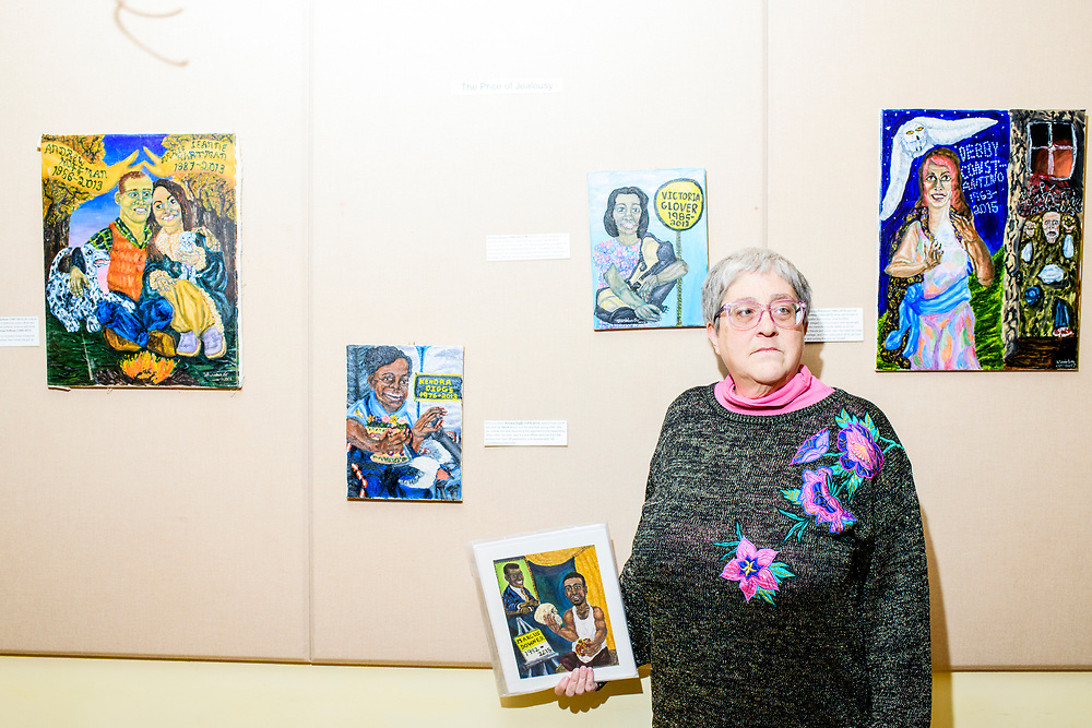 """Baltimore, Maryland - February 03, 2018: Painter Kimberly Sheridan stands for a portrait with her portraits at the """"Bridges for the Ones Left Behind"""" gallery opening at the The Baltimore Ethical Society during the third Baltimore Ceasefire weekend Saturday February 3rd, 2018. She creates a series of painting of people killed by gun violence. <br /> <br /> CREDIT: Matt Roth"""
