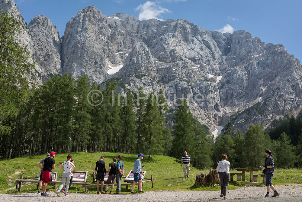 Visitors walk a trail beneath Prisank 2547m a mountain view near the top of Vrsic Pass in the Slovenian Julian Alps, on 22nd June 2018, in Triglav National Park, Slovenia.
