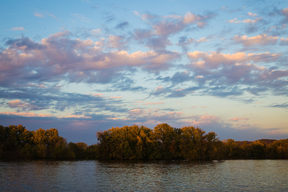Landscape photograph of the Mississippi river towards sundown with trees and clouds.