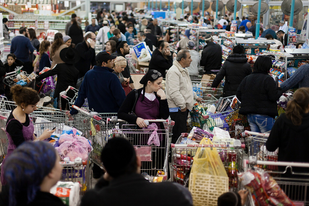 Israeli shoppers wait on a check-out line in a supermarket in Jerusalem, Israel, on March 19, 2013, in preparation ahead of the Jewish holiday of Passover.
