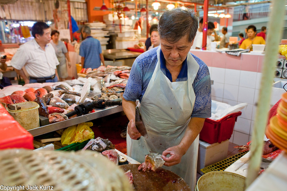 """Apr. 28 -- SINGAPORE:   A butcher chops chicken in a """"wet"""" market in Chinatown in Singapore.    PHOTO BY JACK KURTZ"""