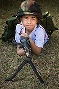"""11 JANUARY 2014 - BANGKOK, THAILAND:  A Thai boy plays with a machine gun during Children's Day in Bangkok. The Royal Thai Army hosted a """"Children's Day"""" event at the 2nd Cavalry King's Guard Division base in Bangkok. Children had an opportunity to look at military weapons, climb around on tanks, artillery pieces and helicopters and look at battlefield medical facilities. The Children's Day fair comes amidst political strife and concerns of a possible coup in Thailand. Earlier in the week, the Thai army announced that movements of armored vehicles through Bangkok were not in preparation of a coup, but were moving equipment into position for Children's Day.     PHOTO BY JACK KURTZ"""