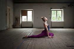 Mid adult woman practicing pigeon pose in yoga studio, Munich, Bavaria, Germany