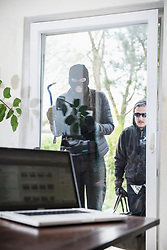 Burglar looking at laptop through window