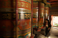 Large Tibetan Prayer Wheels like these might have a mile of prayers inside, bringing the spinner lots of good merit every time they spin one.  This Elderly woman has probably spent her whole life spinning wheels just like these.  Dawu (Dafu), Tibet (China).