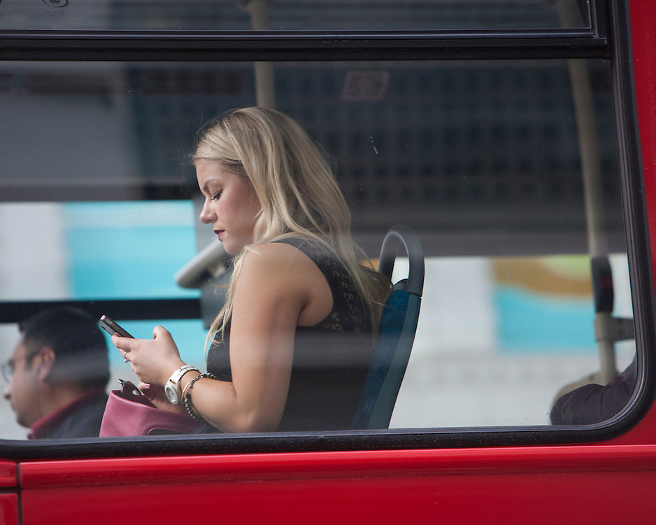 Female commuter on a London bus checking her messages on a digital device