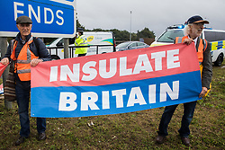 Insulate Britain climate activists stand with a banner after a M25 slip road at Junction 14 close to Heathrow airport was blocked as part of a campaign intended to push the UK government to make significant legislative change to start lowering emissions on 27th September 2021 in Colnbrook, United Kingdom. The activists are demanding that the government immediately promises both to fully fund and ensure the insulation of all social housing in Britain by 2025 and to produce within four months a legally binding national plan to fully fund and ensure the full low-energy and low-carbon whole-house retrofit, with no externalised costs, of all homes in Britain by 2030.