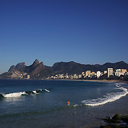 Early morning surfers at Ipanema beach catch a wave as the sunrise catches the light of the surrounding beachfront properties. Ipanema beach, Rio de Janeiro, Brazil. 12th July 2010. ...